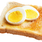Toasted white bread with slices of hard boiled egg isolated on white ** Note: Shallow depth of field
