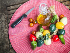 olive oil and fresh vegetables on pink place mat. Mediterranean diet