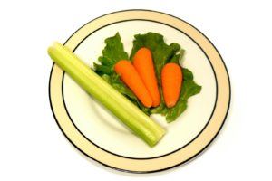 Plate with a very small portion of vegetables isolated over a white background