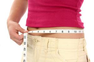 Close-up of woman holding measuring tape around waist.